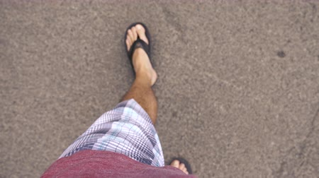 klapki : Walking Looking Down at Flip Flops. view racks focus from stomach and shirt down to feet walking on concrete with flip flops Wideo