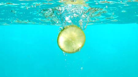 citrón : Lemon Slice is Falling in Blue Water with Bubbles in Slow Motion Underwater Shot Tabletop