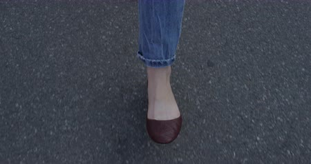 Walking Feet of Woman in two Directions in Jeans on Asphalt in Slow Motion