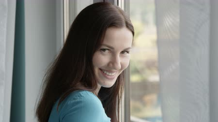 Portrait of a Smiling Female standing by the Window Shot on Red