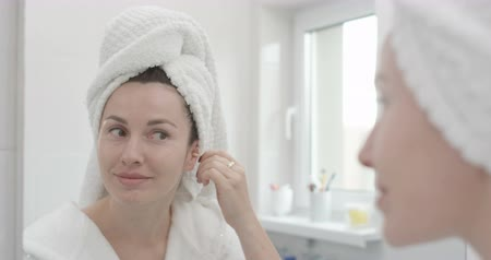 Female is Cleaning Ears with Cotton Swab in Bathroom Shot on Red Epic