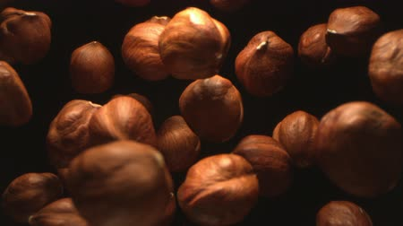 Hazelnut Nuts Flying in the Air in a Free Fall in Slow Motion on Black Background at 1500 fps