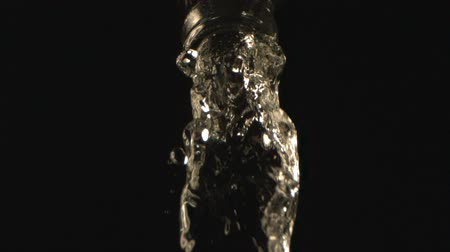 Cold Water Pouring Down from a Bottle Neck in High-Speed on a Black Background