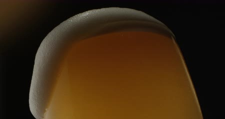 Beer Froth Pouring into a Glass with Golden Background