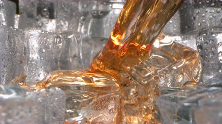 extreme close up : Brandy Whiskey Splashing on Ice in a Glass in Slow Motion