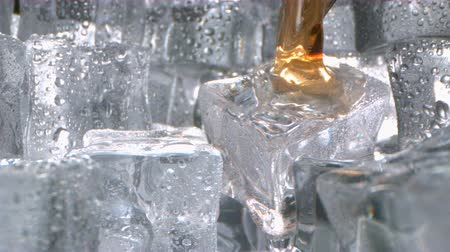 Glass of Splashing Whiskey with Ice in Slow Motion