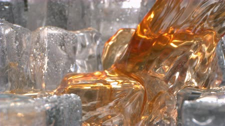 Ice Tea is Pouring on Ice Cubes in Slow Motion