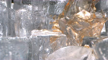 Drinking Whiskey is pouring with Ice inside a Glass in High Speed