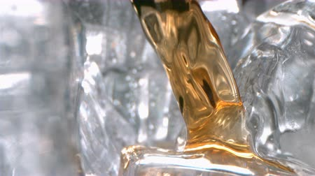 Cognac Alcohol Drink is Flowing and Pouring on Ice in a Glass in High Speed