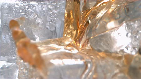 Whiskey with Ice Pouring in a Glass in High Speed Motion