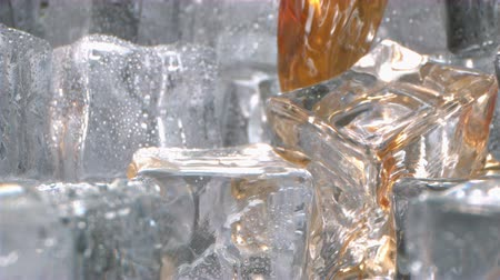 Whiskey is Pouring onto Ice Cubes in a Glass in Slow Motion Camera Dollying Out