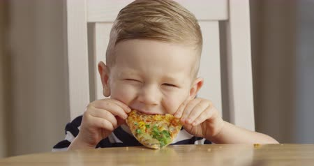 кусаться : Little Boy Eating Pizza Enjoying the Taste and Smiling a Portrait Shot on Red Camera