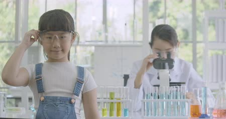 исследование : Portrait of a little asian girl smiling to camera in a chemistry lab with female scientist working in the background