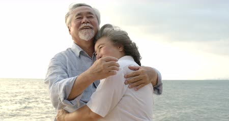 emekli : Asian senior couple embracing each other on the beach.