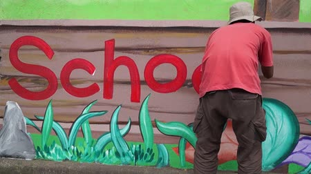 popisný : Mural painter colors the wall