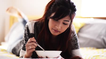 postel : asian girl on bed eating chicken noodle soup