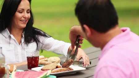 пикник : family eating grilled food at picnic table