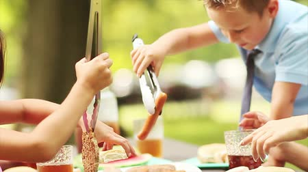 lassú : family eating barbecue meal at park table in slow motion
