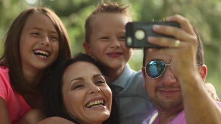 ailelerin : video of a family taking selfies with smartphone in park, shot in 24p frame rate.