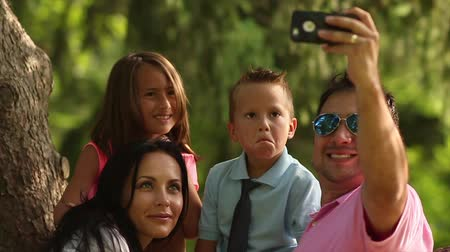 ailelerin : family taking selfies in park