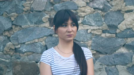 Sad brunette girl with long black hair on a stone wall background. A girl with oriental appearance is dressed in a white T-shirt with a strip