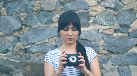 Young brunette girl with long hair adjusts an old retro camera, on the background of an old stone wall. A hipster girl with an oriental appearance is dressed in a white T-shirt with a strip