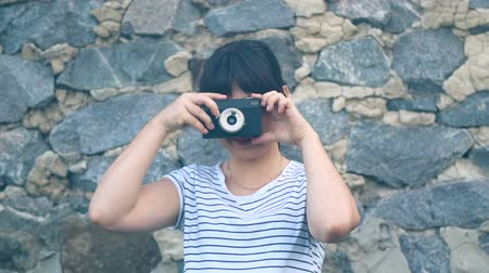 Young brunette girl with long hair photographing on an old retro camera, on the background of a stone wall. A hipster girl with an oriental appearance is dressed in a white T-shirt with a strip