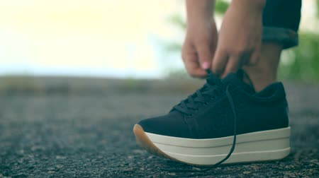 A young girl ties up her shoelaces on black sneakers. Wideo