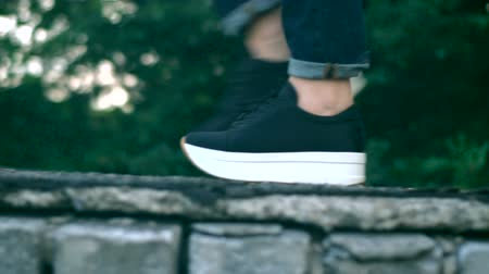 A young girl walks on the edge of the roof in black sneakers. Dostupné videozáznamy