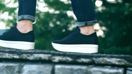 A young girl walks on the edge of the roof in black sneakers. Wideo