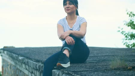 Young brunette girl sits on the roof of a house. A hipster girl with an oriental appearance is dressed in a white T-shirt with a strip Dostupné videozáznamy