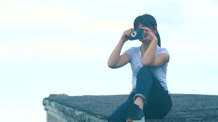 Young brunette girl sits on the roof of a house and takes pictures on an old retro camera. A hipster girl with an oriental appearance is dressed in a white T-shirt with a strip