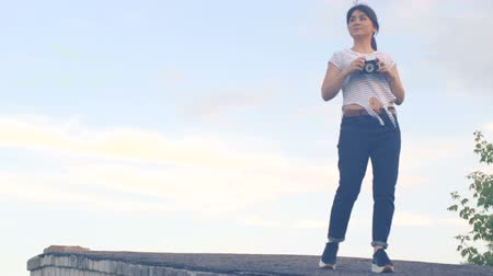 Young brunette girl is walking on the roof of the house and taking pictures on an old retro camera. A hipster girl with an oriental appearance is dressed in a white T-shirt with a strip Dostupné videozáznamy