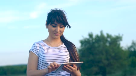 touchpad : Young brunette girl with long hair writes a message on a tablet computer with a touch screen on a nature background