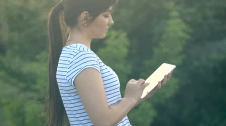 Young brunette girl with long hair writes a message on a tablet computer with a touch screen on a nature background