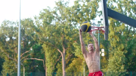 A player in streetball makes a slam dunk. Basketball training outdoors in the park. Healthy lifestyle. Video in full hd format.