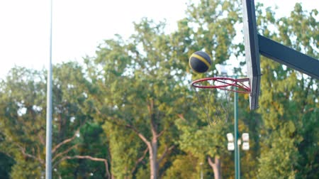 Basketball ball enters the basket. Basketball training outdoors in the park. Healthy lifestyle. Video in full hd format