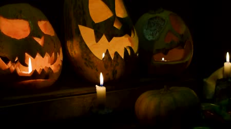 grão : Video background for halloween. Three pumpkins with candles. Smooth vertical slide video with full HD quality