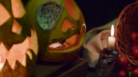 roliço : Video background for halloween. Three pumpkins with candles in a basket with vegetables. Smooth horizontal slide video with full HD quality
