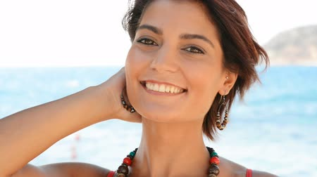 Beautiful young woman laughing and have fun at summer beach. She is a beautiful tanned hispanic girl.