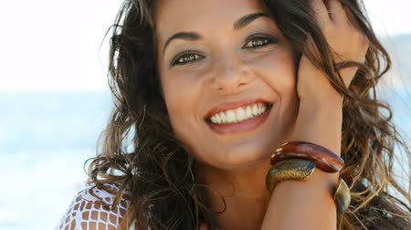 looking : Portrait of smiling brunette girl looking at camera at seaside. Happy carefree young woman relaxing and looking at camera on summer vacation at sea.