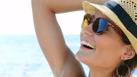 шляпа : Happy girl at sea. Portrait Of Smiling Young Woman Wearing Sunglasses. Happy girl with straw hat at seaside. Carefree brunette woman relaxing at sea.
