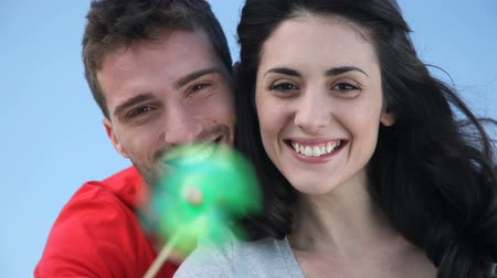 genç çift : Happy smiling couple playing with a toy windmill outdoor symbol of environmental conservation and renewable energy. Portrait of joyful young man and young woman looking at camera outdoor.