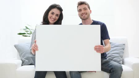 сидеть : Portrait Of Smiling Young Couple Holding Placard At Home. Happy girl and smiling guy looking at camera with blank sign. Happy couple sitting on couch an holding a white placard. Стоковые видеозаписи