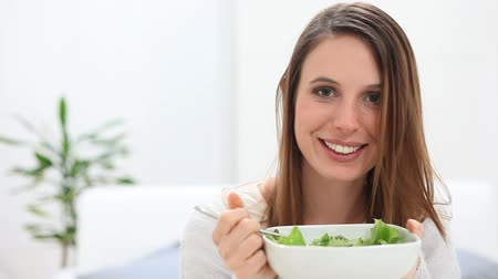 comer : Portrait of young beautiful woman eating fresh salad at home. Happy girl have a launch in her home. Smiling woman on a diet sitting and looking at camera. A vegetarian girl eating a salad.