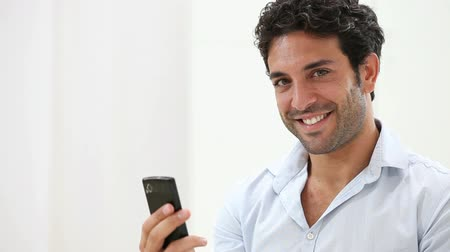 spojrzenie : Good Looking Man Sitting On Sofa And chatting On Mobile Phone. Smiling guy typing on smartphone and looking at camera. Portrait of happy young man checking the email with telephone. Wideo
