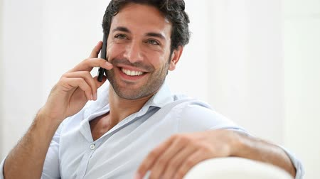mluvení : Young man smiling and talking on smart phone at home. Happy guy sitting on couch and talking on telephone. Joyful guy laughing at phone.
