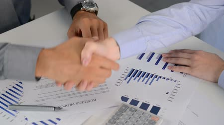 tratar : Close Up Of Businesspeople Shaking Hands At Desk. Conclusion of a new business deal between a businessman and a businesswoman. Close up of a handshake for a new financial agreement. Vídeos