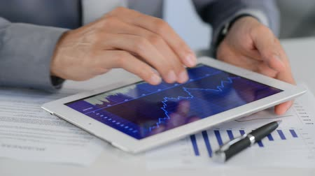 сообщить : Close Up Of A Businessman Analyzing Graph On Digital Tablet. Hands of a businessman who studies the market trends through a graphic on tablet. A business man checks the successful business with a chart of positive performance. Стоковые видеозаписи
