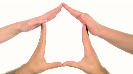 инвестирование : Four hands forming a house on a white background. Close up of handsshaped house. A couple plan to move house together. Feeling safe at home.
